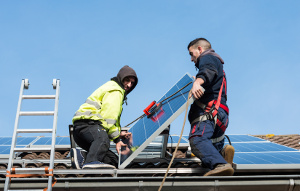 Two men install solar panels on a roof
