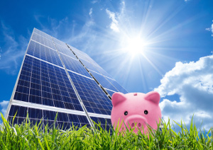 Money piggy bank standing on grass in front of a solar panel